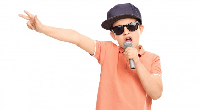 Little boy in hip hop outfit rapping on a microphone
